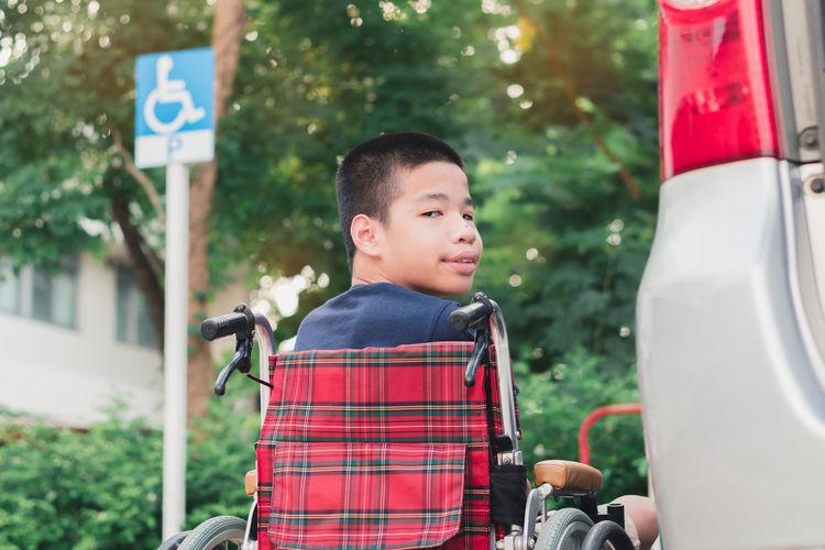 Portrait of boy sitting on wheelchair by car