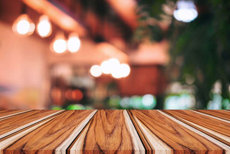 Close-Up Of Wooden Table Against Illuminated Lights