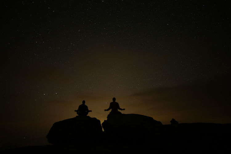 Silhouette people sitting on rock against sky at night