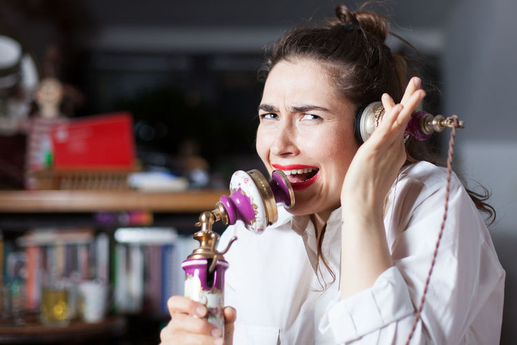 Portrait of woman screaming on old-fashioned telephone at home