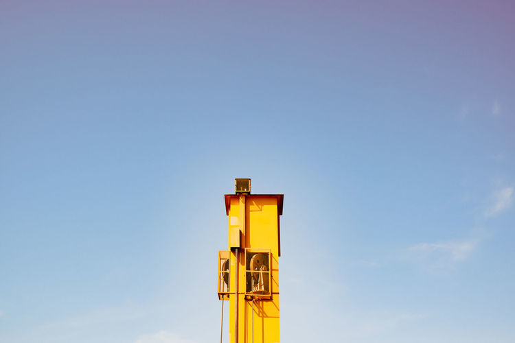 Low angle view of yellow tower against sky