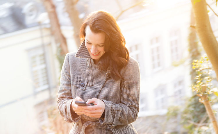 beautiful businesswoman with mobile phone outside Brunette Buisness Casual Clothing Confidence  Front View Handy Lens Flare Lifestyles Liv Tyler London Looking At Camera Person Portrait Real People Serious Sexygirl Smiling Sunlight Village Waist Up Young Adult Young Women