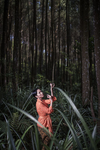 Side view of young woman dancing at forest