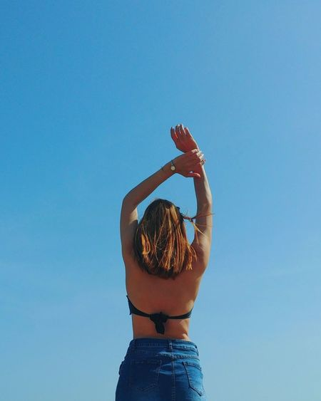 Rear view of woman standing with arms raised against clear blue sky
