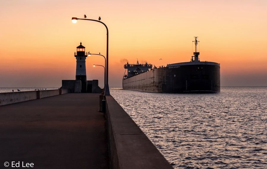 Duluth harbor entrance Shipping  Beauty In Nature Minnesota Streamzoofamily Malephotographerofthemonth Sunset Sky Orange Color Built Structure Architecture Water Street Light Transportation
