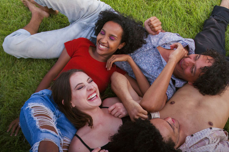 Bonding Casual Clothing Cheerful Day Enjoyment Friendship Fun Grass Happiness High Angle View Leisure Activity Lifestyles Love Lying Down Lying On Back Men Outdoors Relaxation Shirtless Smiling Summer Togetherness Young Adult Young Men Young Women