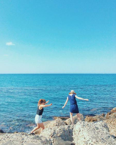 Friends on beach against clear blue sky