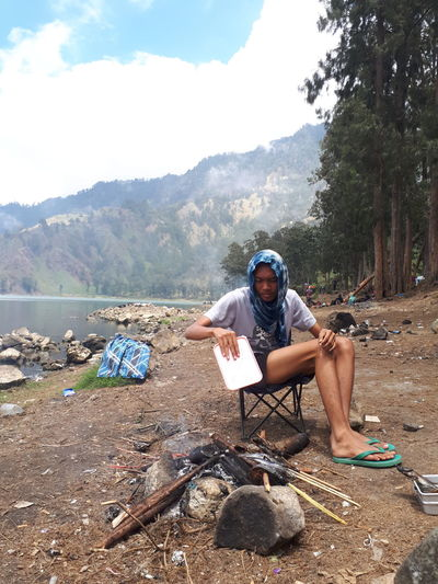 Full length of man holding camera while sitting on land
