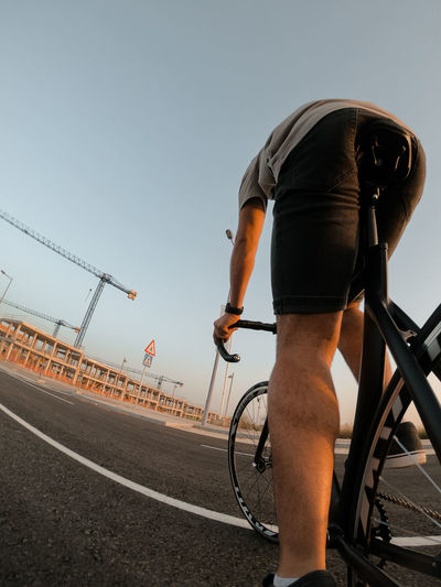 Man riding bicycle on road against clear sky