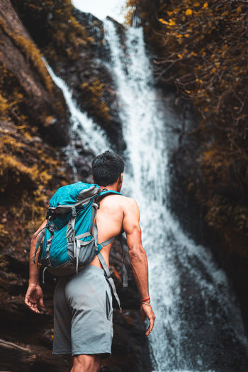 Rear view of man against waterfall