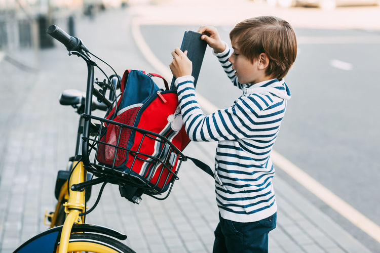 Boy in a striped sweater puts a tablet in a backpack that hangs on the handlebars of a bicycle