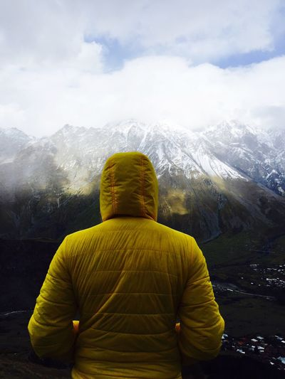 Rear view of man standing against mountain during winter