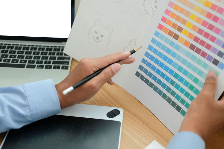 Cropped hand of businessman holding color swatch in office