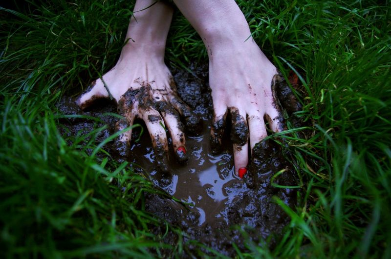 Cropped Image Of Hand Touching Wet Mud On Field