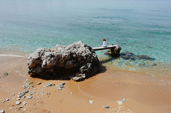 High angle view of girl sitting on rock at beach