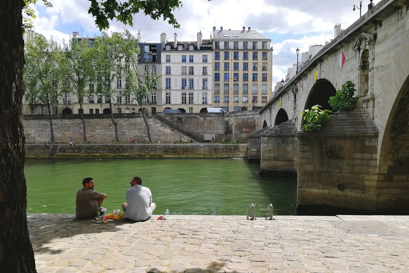 People sitting by canal against buildings