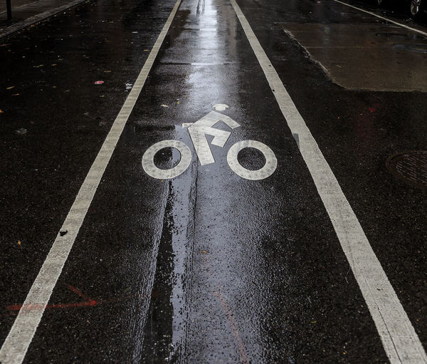 Bike lane in New York, from here to eternity. Sign Marking Road Symbol Road Marking Communication Transportation Direction The Way Forward Guidance High Angle View Asphalt City Day No People Road Sign Bicycle Lane Street Wet Information Rain Outdoors Dividing Line Rainy Season Surface Level