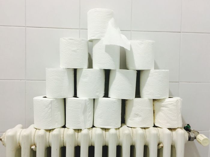Stack of tissue papers on radiator against tiled wall