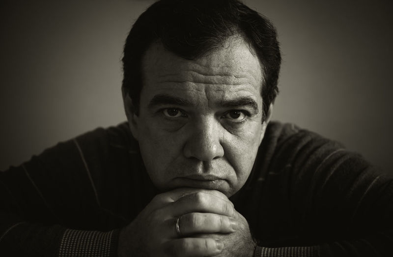 Portrait Of Serious Mature Man With Hands On Chin Against Gray Background