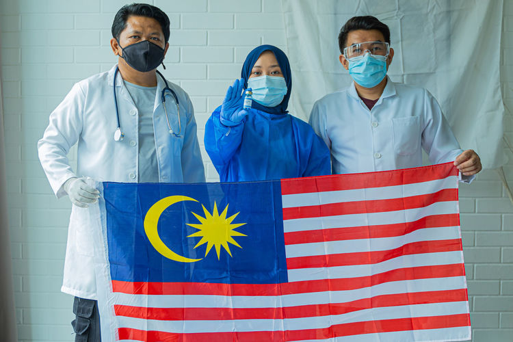 Frontliner concept, malaysian people wearing medical suit holding flag