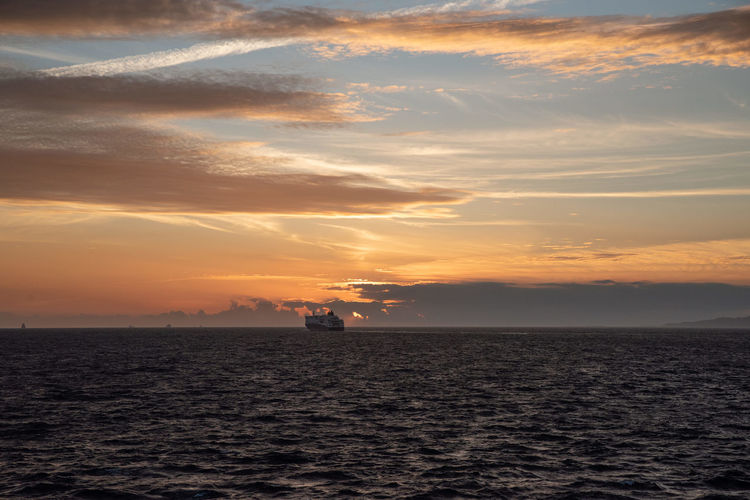 Ships sailing in the mediterranean sea with a sunset