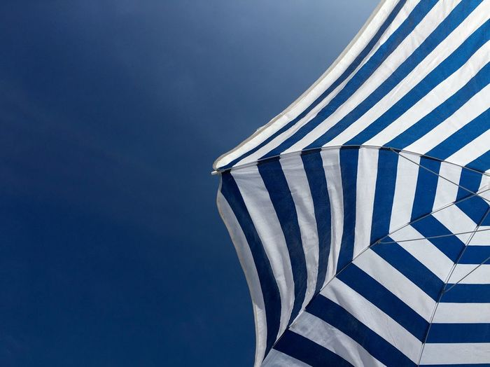 Low angle view of white and blue beach umbrella against blue sky