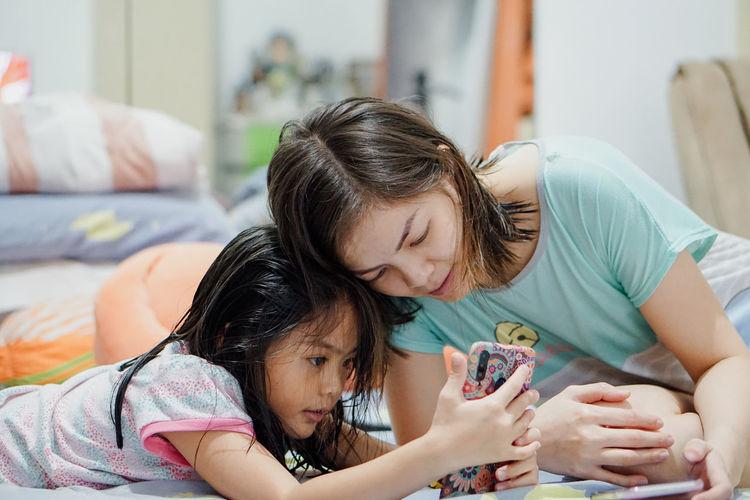 Girl and woman using mobile phone