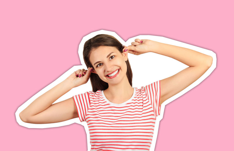 Portrait of a smiling young woman against pink background