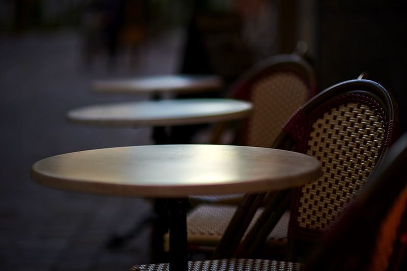 Empty chairs and tables at outdoor cafe