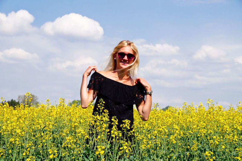 Portrait of smiling young woman standing on oilseed rape field