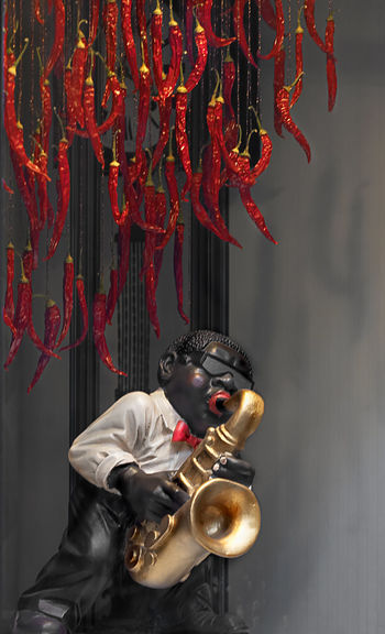 Red chili peppers hanging over figurine with saxophone