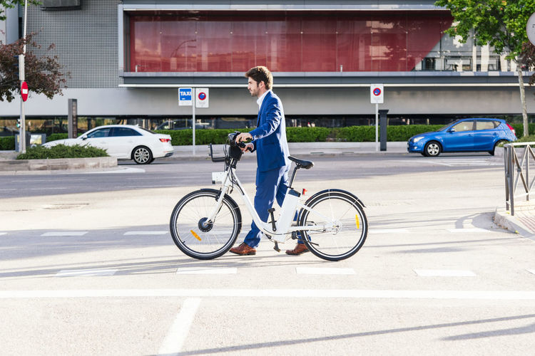 Side view of man riding bicycle on road