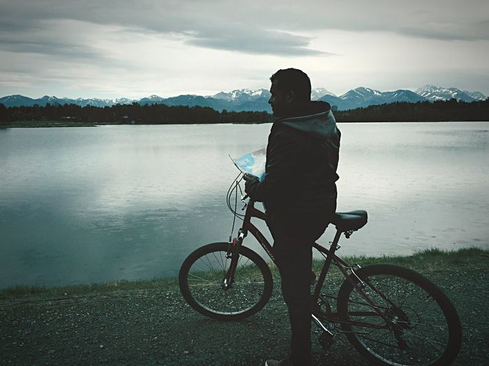 Man With Bicycle And Map By Lake Against Sky