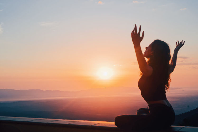 Silhouette woman with arms raised against sky during sunset