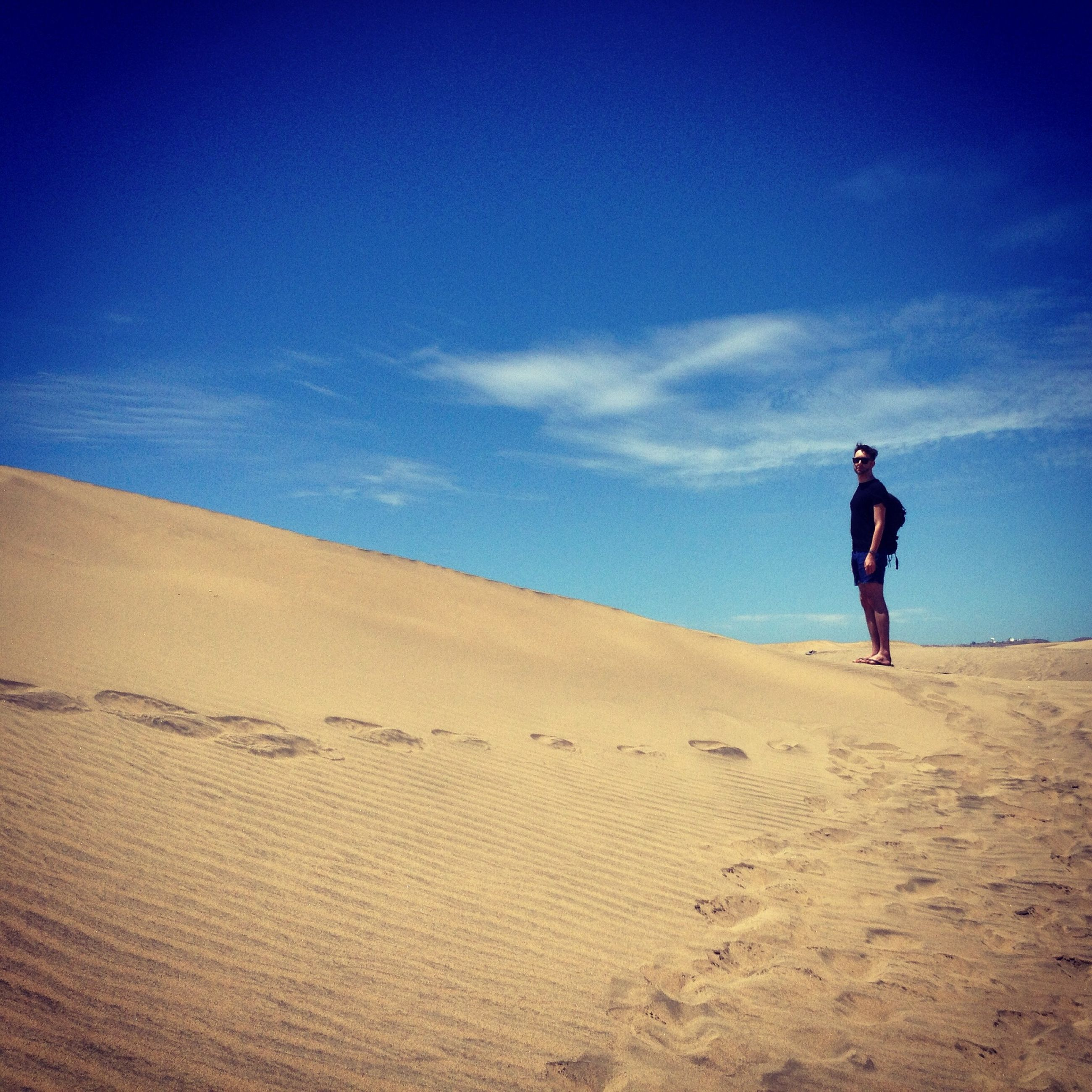 full length, lifestyles, leisure activity, sky, men, casual clothing, rear view, blue, landscape, standing, walking, tranquility, tranquil scene, sand, nature, cloud - sky, cloud, scenics