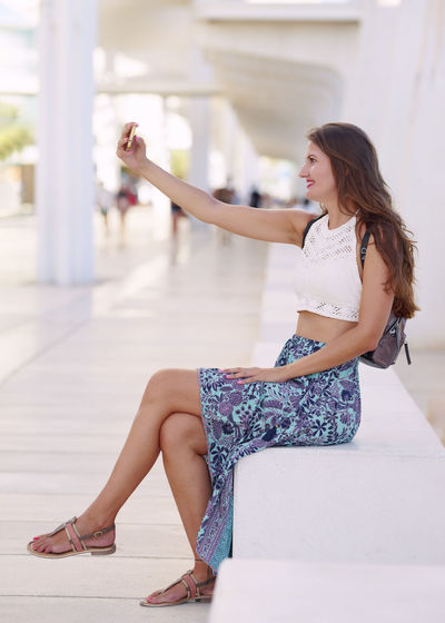 Side view of woman sitting outdoors