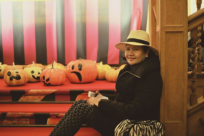 Side view portrait of woman sitting by jack o lanterns
