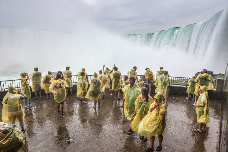 People wearing raincoats while standing in front of niagara falls