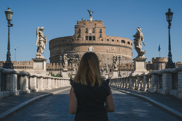 Rear view of woman standing against statue in city