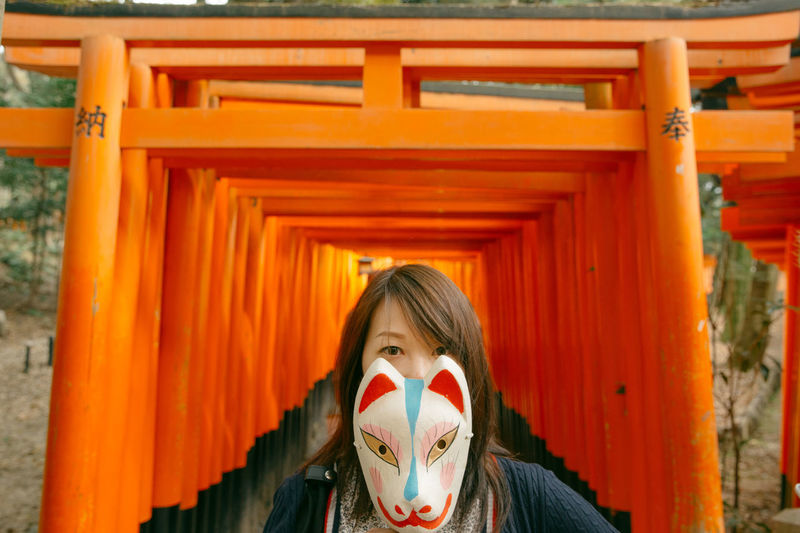 Portrait Of Young Woman Holding Mask Against Torii Gates