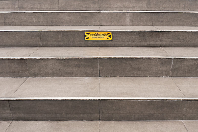 "Paved grey public steps with a yellow ""Beware your step"" caution sign. Caution Sign Stairs Steps Architecture Beware City Day No People Outdoors Warning Warning Sign Yellow"