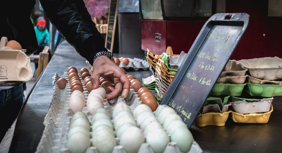 Midsection of man holding eggs for sale at market stall