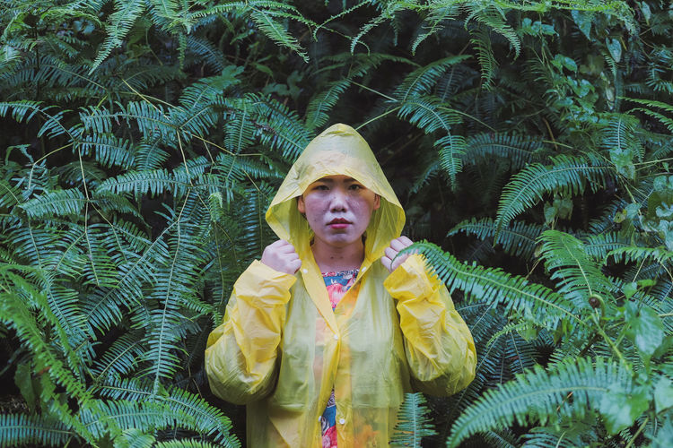 Portrait of woman in raincoat standing against plants