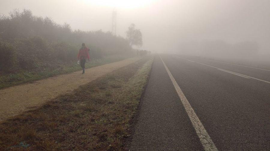 Woman Walking On Footpath By Road In Foggy Weather