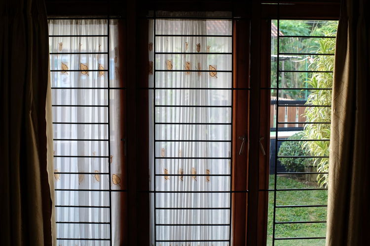Light curtains on a window, one part of which is open, showing a garden view on the outside