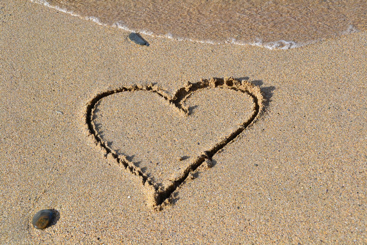 Heart shape on sand at beach during sunny day