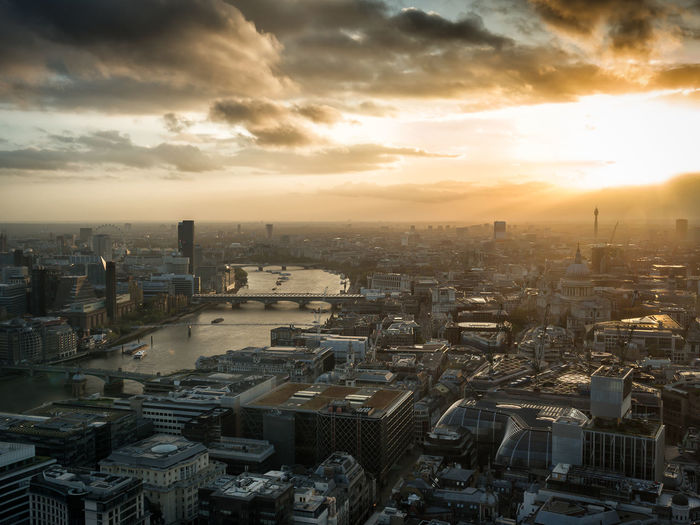 High angle view of thames river amidst cityscape against cloudy sky