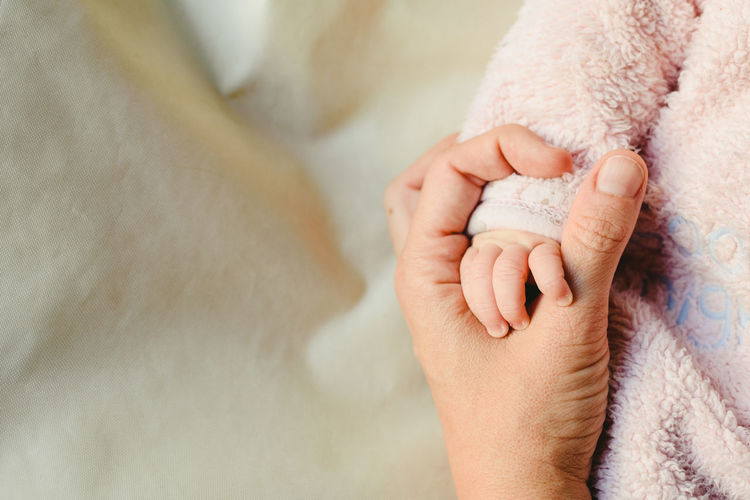 Cropped hand of mother holding baby girl hand