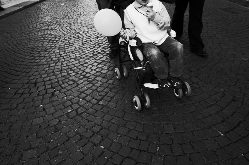 Low section of person with balloon and ice cream on wheelchair