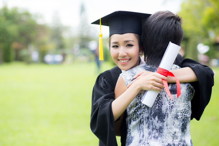 Achievement Happiness Graduation Gown Graduation Smiling Emotion Student Mortarboard Women Portrait University Education Real People Young Adult Day Focus On Foreground Standing Nature Two People University Student Outdoors Positive Emotion